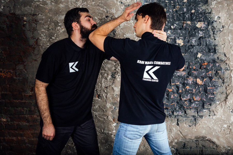 krav maga student strikes attacker with elbow uppercut